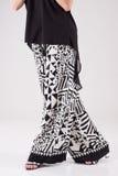 Blusa femenina del negro del traje y pantalones blancos y negros anchos Foto de archivo libre de regalías