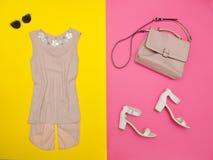 Blusa poner crema, bolso, zapatos blancos y vidrios Fondo rosado-amarillo brillante Fotos de archivo libres de regalías
