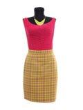Blusa rosada y falda de tela escocesa amarilla de neón en maniquí. Fotografía de archivo