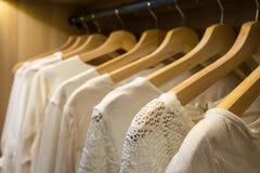 Blusas y suéteres blancos en suspensiones en un guardarropa imagen de archivo