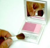 Blush. Reflection image on a mirror on someone using blush Stock Photography