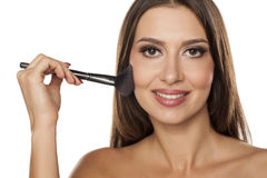 Blush apply. Young woman applying blush with a brush Royalty Free Stock Photos