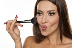 Blush apply. Young woman applying blush with a brush Stock Images