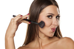 Blush apply. Young woman applying blush with a brush Royalty Free Stock Images