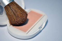 Blush brush and blusher. Closeup shot of a blush brush placed on top of peach coloured blusher stock image