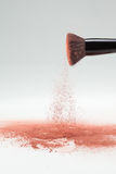 Blush brush shaking off pink loose powder blush Stock Images