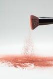 Blush brush shaking off pink loose powder blush. A lateral view of a flat blush brush, shaking off pink loose powder blush, shot on a white backgrownd Stock Images