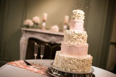 Blush and Cream Wedding Cake in front of a fireplace. With a diamond rhinestone letter `V` topper Stock Photography