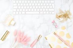 Blush and gold feminine desktop with makeup and keyboard. Copy sp. Blush and gold feminine desktop with makeup and keyboard Stock Photography