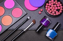 Blush powder, nail polish, sponges and brushes on black slate Stock Images