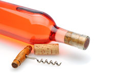 Blush Wine Bottle 0n White. Closeup of a blush wine bottle and corkscrew laying on a white background with reflection and shadow Stock Photo