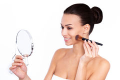 Blushing beauty. Shot of a beautiful young woman applying blush with a makeup brush holding mirror against white isolated background Stock Photo