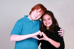Blushing Boy and Girl Couple. Teen caucasian couple with boy blushing making a heart with hands Stock Image