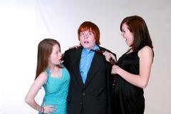 Blushing boy and girls. Two caucasian teen girls fighting over blushing boy Royalty Free Stock Image