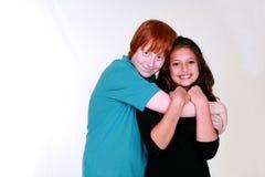 Blushing boy Teen Couple Hugging. Closeup of real people teen caucasian couple and boy blushing Royalty Free Stock Photos