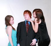 Blushing boy and teen girls flirting. Two caucasian teen girls fighting over blushing boy Royalty Free Stock Photo