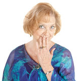Blushing Grandmother. Blushing Caucasian grandmother with hand over mouth Royalty Free Stock Photos