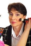 Blushing mature woman cheeks. Beautician hand blushing mature woman cheeks against white background Stock Image