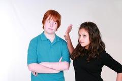Blushing teen boy and angry girl stock photos