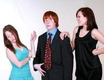 Blushing teen boy with girls. Two caucasian teen girls fighting over blushing boy Royalty Free Stock Images