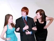 Blushing Teen boy with two girls. Two caucasian teen girls fighting over blushing boy Stock Photos