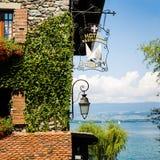 Bluszcz Zakrywająca Kamienna ściana z Czerwonymi kwiatami, łodziami i jeziorem na słońcu, zdjęcia royalty free