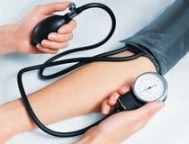 Blutdruck, der auf weißem Hintergrund misst Stockfotografie