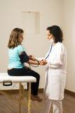 Blutdruck des Doktor-Taking Girls. Vertikal Stockfotografie