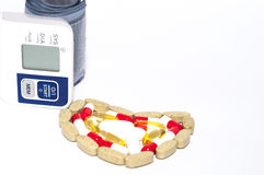 Blutdruckkontrolleur und bunte Tabletten vereinbarten in der Herzform lizenzfreies stockbild