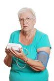 Blutdruckmaschine des älteren Frauengebrauches automatische Lizenzfreie Stockbilder