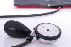 Blutdruckmesser, das auf weißer Tabelle liegt Stockfotografie