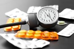 Blutdruckmeter und -pillen auf der Tabelle Stockbilder