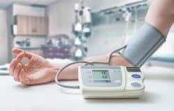 Blutdruckmonitor, -pillen und -spritze lokalisiert auf weißem Hintergrund Mann misst Blutdruck mit Monitor im Krankenhaus Lizenzfreies Stockfoto