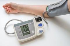 Blutdruckmonitor, -pillen und -spritze lokalisiert auf weißem Hintergrund Mann misst Blutdruck mit Monitor Lizenzfreie Stockfotografie