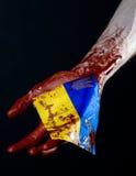 Blutige Hände, die Flagge von Ukraine im Blut, Revolution in Ukraine, schwarzer Hintergrund Stockbild