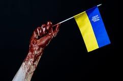 Blutige Hände, die Flagge von Ukraine im Blut, Revolution in Ukraine, schwarzer Hintergrund Lizenzfreies Stockfoto