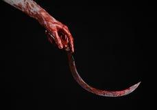 Blutige Hand, die eine Sichel, Sichel blutig, blutige Sense, blutiges Thema, Halloween-Thema, schwarzer Hintergrund, lokalisiert  stockbilder
