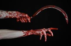 Blutige Hand, die eine Sichel, Sichel blutig, blutige Sense, blutiges Thema, Halloween-Thema, schwarzer Hintergrund, lokalisiert  stockfotografie