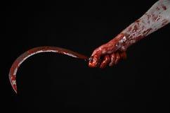 Blutige Hand, die eine Sichel, Sichel blutig, blutige Sense, blutiges Thema, Halloween-Thema, schwarzer Hintergrund, lokalisiert  lizenzfreie stockfotografie