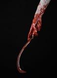 Blutige Hand, die eine Sichel, Sichel blutig, blutige Sense, blutiges Thema, Halloween-Thema, schwarzer Hintergrund, lokalisiert  lizenzfreie stockbilder