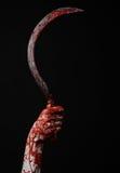 Blutige Hand, die eine Sichel, Sichel blutig, blutige Sense, blutiges Thema, Halloween-Thema, schwarzer Hintergrund, lokalisiert  lizenzfreie stockfotos
