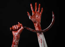 Blutige Hand, die eine Sichel, Sichel blutig, blutige Sense, blutiges Thema, Halloween-Thema, schwarzer Hintergrund, lokalisiert  stockfoto