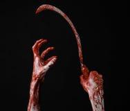 Blutige Hand, die eine Sichel, Sichel blutig, blutige Sense, blutiges Thema, Halloween-Thema, schwarzer Hintergrund, lokalisiert  stockbild