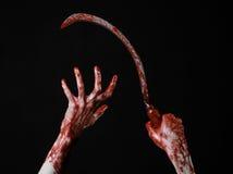 Blutige Hand, die eine Sichel, Sichel blutig, blutige Sense, blutiges Thema, Halloween-Thema, schwarzer Hintergrund, lokalisiert  stockfotos