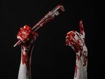 Blutige Hand, die einen justierbaren Schlüssel, blutigen Schlüssel, verrückter Klempner, blutiges Thema, Halloween-Thema, schwarz Stockfotografie