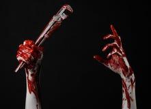 Blutige Hand, die einen justierbaren Schlüssel, blutigen Schlüssel, verrückter Klempner, blutiges Thema, Halloween-Thema, schwarz Lizenzfreie Stockfotos
