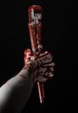 Blutige Hand, die einen justierbaren Schlüssel, blutigen Schlüssel, verrückter Klempner, blutiges Thema, Halloween-Thema, schwarz Lizenzfreie Stockfotografie