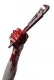 Blutige Hand, die einen justierbaren Schlüssel, blutigen Schlüssel, verrückter Klempner, blutiges Thema, Halloween-Thema, weißer  Lizenzfreies Stockfoto