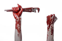 Blutige Hand, die einen justierbaren Schlüssel, blutigen Schlüssel, verrückter Klempner, blutiges Thema, Halloween-Thema, weißer  Lizenzfreie Stockbilder