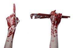 Blutige Hand, die einen justierbaren Schlüssel, blutigen Schlüssel, verrückter Klempner, blutiges Thema, Halloween-Thema, weißer  Stockbilder